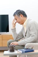 額に手をあてる中高年日本人男性