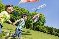 公園で鯉のぼりの下を走る日本人の男の子たち