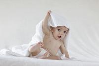 頭からタオルをかけて座っている外国人の赤ちゃん