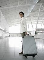 スーツケースを持って立つ日本人男性