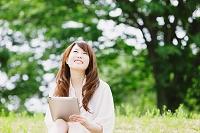 新緑とiPadを持つ日本人女性