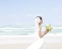 海辺でウェディングドレスを着て立つ花嫁