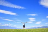 青空に向かって手を広げる女子校生