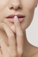 唇を触る白人女性の指