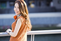 街中の川沿いに立つ日本人女性