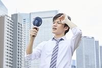 携帯扇風機を使う日本人ビジネスマン