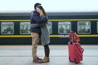 駅で抱き合う若いカップル
