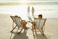 砂浜でリラックスする外国人家族