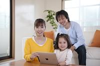 パソコンを見る母と娘とソファに座る父