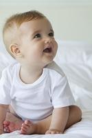 ベッドに座る男の子の赤ちゃん