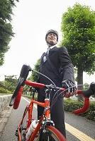ヘルメットをかぶった若い男性と自転車