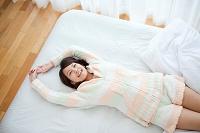 ベッドで横になっている日本人女性