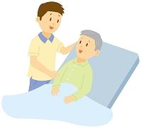介護ベッドにもたれる老人と介護士