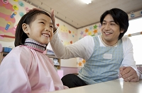 女の子の頭を撫でる幼稚園教諭
