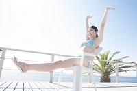 伸びをする水着姿の日本人女性