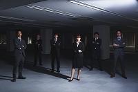 暗いオフィスに立つビジネスパーソン