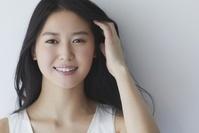 笑顔の髪をかきあげる日本人女性