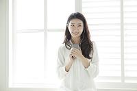 スマートフォンで音楽を聴く20代日本人女性