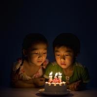 ケーキのろうそくを見る日本人の子供