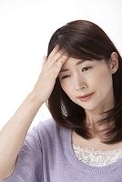 発熱で頭に手をやる女性