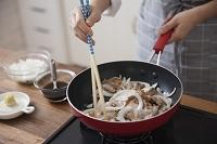 豚薄切り肉と玉ねぎをフライパンで焼く女性