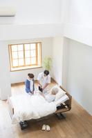 在宅医療する医者と看護師とシニア女性患者