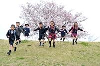 桜の公園を駆け降りる日本人の子供達