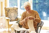 リビングで編み物をするシニア女性