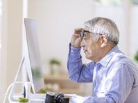 眼鏡を上げてモニターを見るシニアの日本人男性