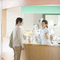ナースステーションで話をする患者と看護師