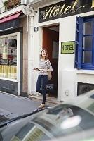 ホテルの前に立つ旅行者の女性