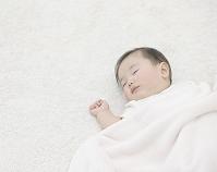 カーペットの上で眠る日本人の赤ちゃん