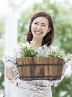 鉢植えを持つ40代の日本人女性