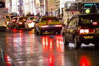 濡れた地面に反射したタクシーのテールライト