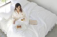 ベッドで朝食を食べる日本人女性
