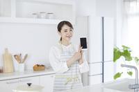 スマートフォンを見せる日本人女性