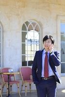 電話をしながらカフェの前を歩く日本人ビジネスマン