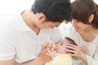 赤ちゃんにミルクをあげる両親