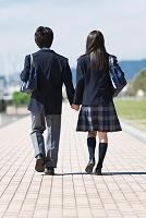 手を繋いで歩いている中高生の男女の後姿
