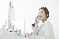オフィスで電話を使うビジネスウーマン