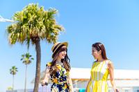 キャリーバッグを引き歩く海のリゾートへ旅する女性2人