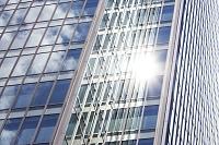 オフィスビルの窓に反射する太陽