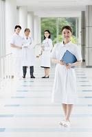 廊下にいる笑顔の若い日本人女性看護師と医療スタッフ