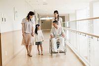 車椅子の60代男性と日本人家族