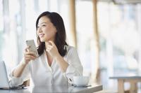 カフェでスマートフォンを使う日本人女性