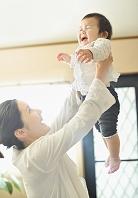 赤ちゃんを持ち上げる母親