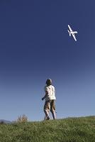 空飛ぶ飛行機模型を見つめる少年