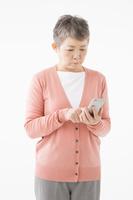 スマートフォンを操作するシニアの日本人女性