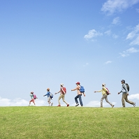リュックを背負い草原を歩く日本人の三世代家族