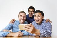 スマートフォンを見る日本人男性と外国人男性